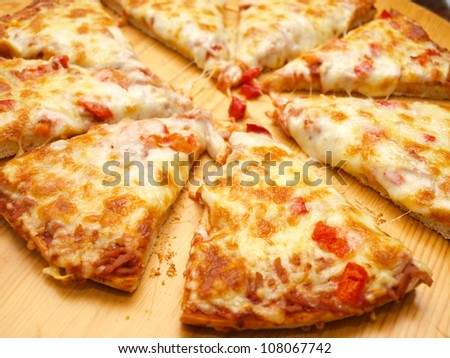 Sliced fresh pizza with red pepper on wooden board - stock photo