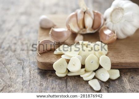 sliced garlic, garlic clove, garlic bulb place on chopping block on vintage wooden backgorund - stock photo
