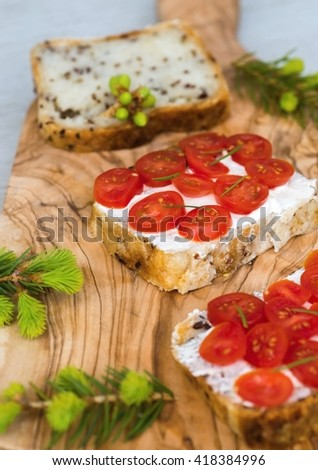 Sliced gluten free bread with cherry tomato and spruce needle twig with gemma on wooden kitchen board on light table