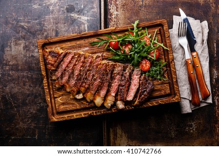 Sliced grilled beef barbecue Striploin steak and salad with tomatoes and arugula on cutting board on dark background - stock photo