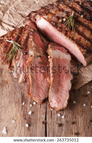 sliced grilled beef steak on a wooden table. vertical view above, rustic style  - stock photo