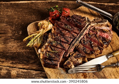 Sliced grilled large t-bone steak in front of roasted garlic and tomato placed on cutting board over old splintering table - stock photo