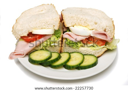 Sliced ham and salad sandwich isolated on a white background.