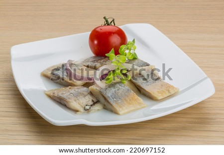 Sliced herring with oregano on the plate - stock photo