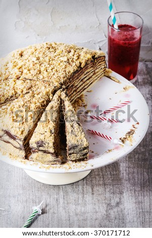 Sliced Homemade Birthday Honey Cake with chocolate cream, served on white ceramic plate over white wooden table with b-day candles and glass of red juice. With plastered wall. Retro filter effect - stock photo