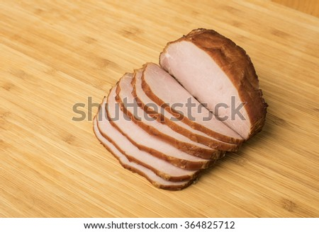Sliced homemade Canadian bacon on pale wood cutting board - stock photo