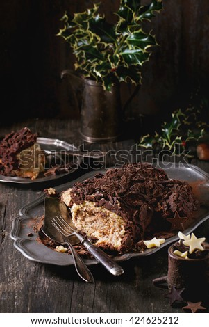 Sliced homemade Christmas chocolate yule log with chestnuts cream on vintage plate with forks,  chocolate stars and holly branch over old wooden table. Dark rustic style. - stock photo