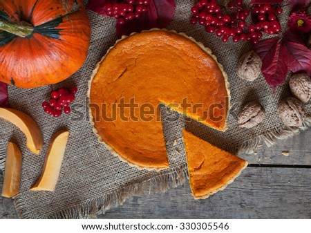Sliced homemade pumpkin tart pie sweet dessert food with nuts and autumn composition on vintage wooden table background. Rustic style and natural light - stock photo