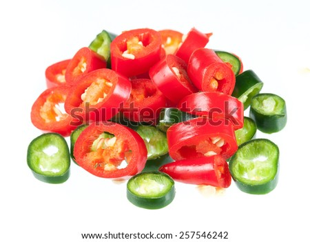 Sliced in pieces red and green chili peppers isolated over white background - stock photo