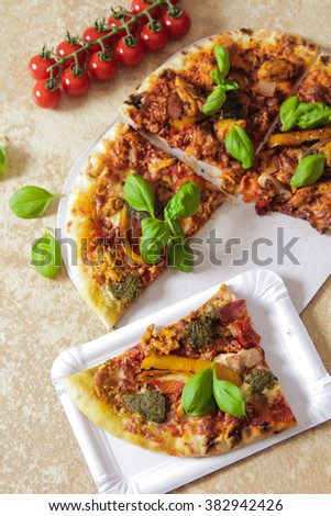 Sliced Italian pizza with basil and cherry tomatoes yellow pepper