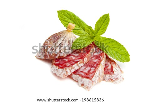 Sliced Italian salami with fresh herbs on a wooden board. Isolated on white - stock photo