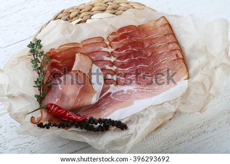 Sliced jamon with thyme on wood background