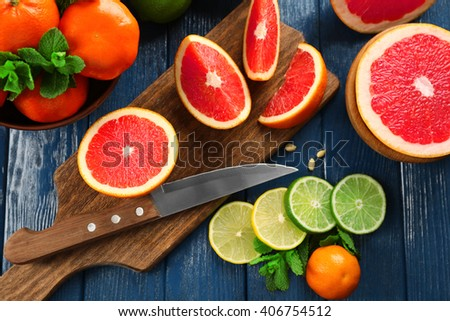 sliced juicy fruits on wooden board, close up - stock photo