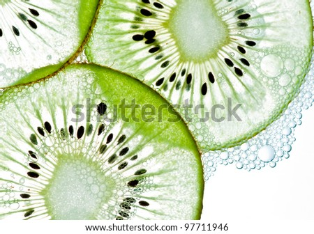 Sliced kiwi covered with bubbles in water isolated on a white background. - stock photo
