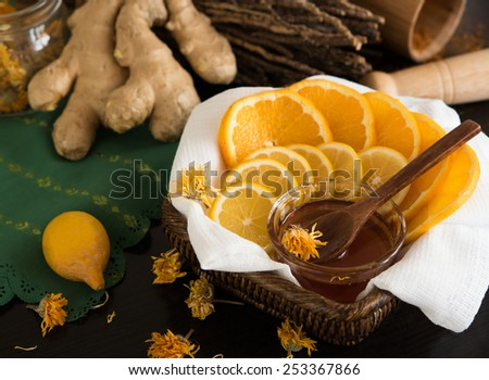 Sliced lemon and orange in busket with honey, ginger root, dry branches, whole lemon and mortar behind. Closeup on wooden teaspoon in honey - stock photo