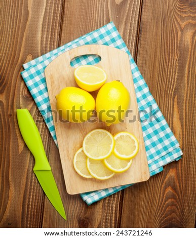 Sliced lemon fruits on cutting board over wooden table. View from above - stock photo