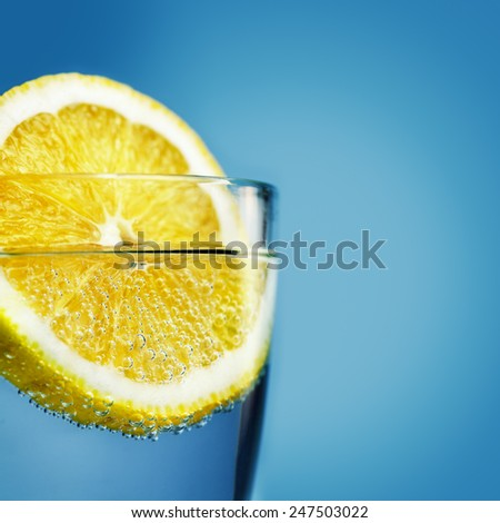 Sliced lemon in glass of water close-up with shallow depth of field - stock photo