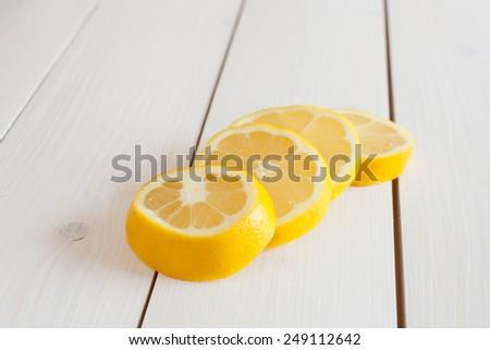 sliced lemon on white wooden board - stock photo