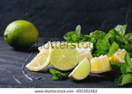Sliced Lime and lemons with bunch of fresh mint on black slate stone board over black textured background - stock photo