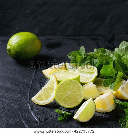 Sliced Lime and lemons with bunch of fresh mint on black slate stone board over black textured background. Square image - stock photo