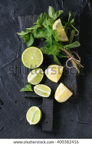 Sliced Lime and lemons with bunch of fresh mint on black wooden chopping board over black textured background. Top view - stock photo