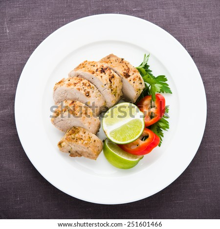 Sliced lime pork tenderloin on dark canvas background top view. - stock photo