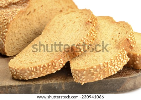 sliced loaf of bread on a cutting board isolated on white - stock photo