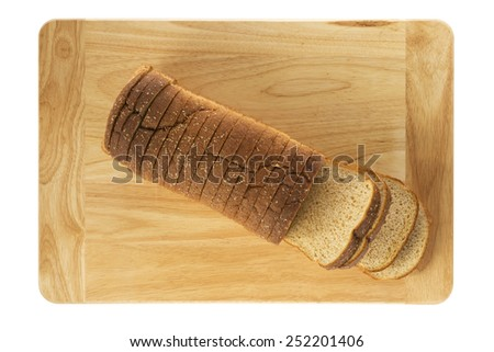Sliced loaf of whole wheat bread on cutting board as viewed from top - stock photo