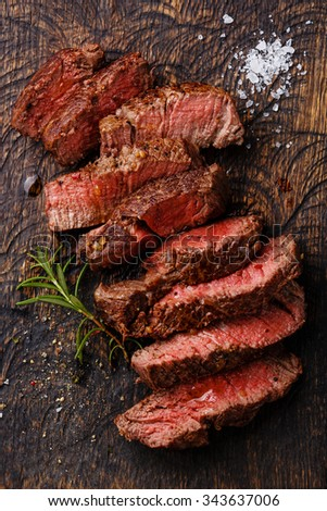 Sliced medium rare grilled Beef steak on wooden cutting board background - stock photo