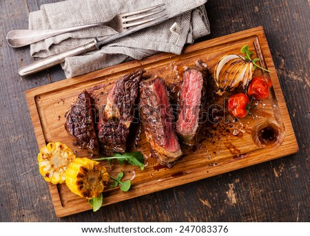 Sliced medium rare grilled Beef steak Ribeye with corn and cherry tomatoes on cutting board on wooden background - stock photo