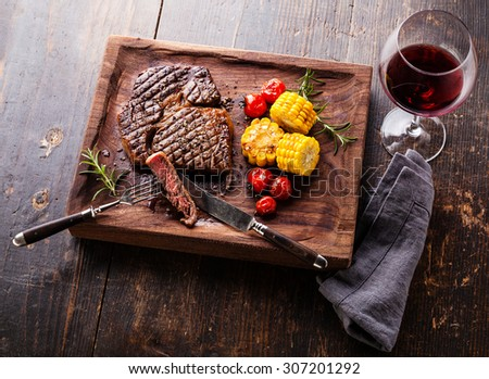 Sliced Medium rare grilled Steak Ribeye Black Angus with corn and cherry tomatoes on serving board block on wooden background - stock photo