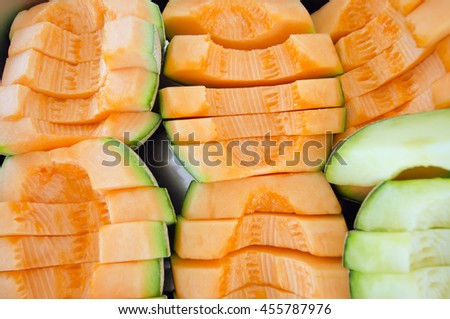 Sliced melon in pieces arranged on steel tray (Other names are cantelope, cantaloup, honeydew, Crenshaw, casaba, Persian melon, and Santa Claus or Christmas melon) - stock photo