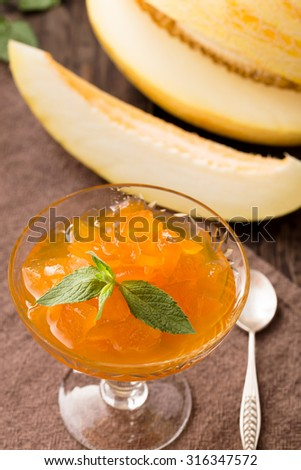 Sliced melon preserved in syrup on table - stock photo