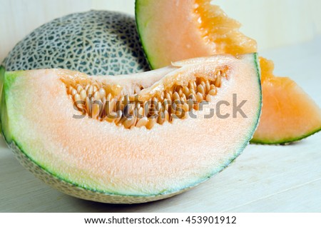 Sliced melon with seed on wooden board (Other names are cantelope, cantaloup, honeydew, Crenshaw, casaba,  Persian melon, and Santa Claus or Christmas melon) - stock photo