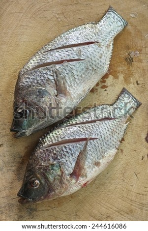 Sliced Nilotica Fish on chopping block wood  - stock photo