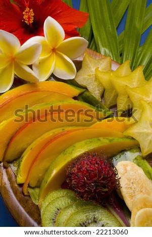 sliced pineapple,kiwi, and papaya from Hawaii with plumeria blossoms - stock photo