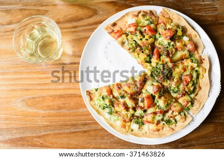 Sliced pizza on white plate with drink in glass on wooden table