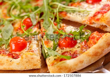 Sliced pizza with arugula and cherry tomatoes on wooden board - stock photo
