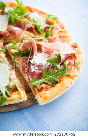 Sliced pizza with prosciutto (parma ham), arugula (salad rocket) and parmesan on blue wooden background close up. Italian cuisine. - stock photo