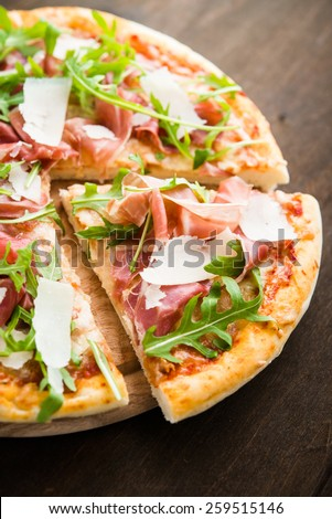 Sliced pizza with prosciutto (parma ham), arugula (salad rocket) and parmesan on dark wooden background close up. Italian cuisine. - stock photo