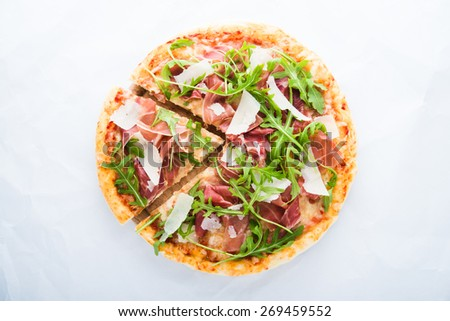 Sliced pizza with prosciutto (parma ham), arugula (salad rocket) and parmesan on white background top view. Italian cuisine. - stock photo