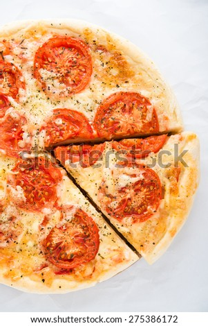 Sliced pizza with tomato, cheese and dry basil on white background top view. Italian cuisine. - stock photo