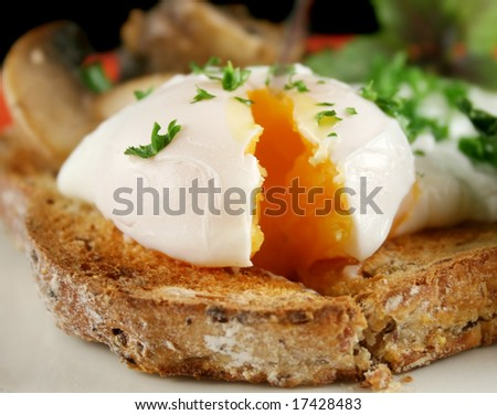 Sliced poached egg breakfast with blanched spinach with mushrooms and shallots. - stock photo