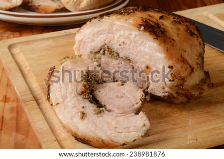 Sliced porchetta pork roast on a cutting board - stock photo
