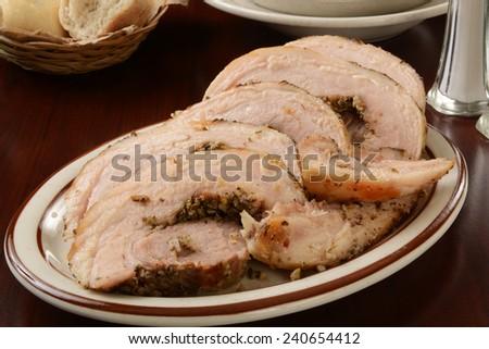 Sliced Porchetta pork roast on a serving platter - stock photo