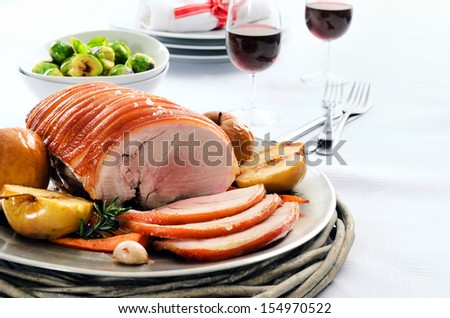 Sliced pork roast served at a table set with vegetable sides, wine and cutlery - stock photo