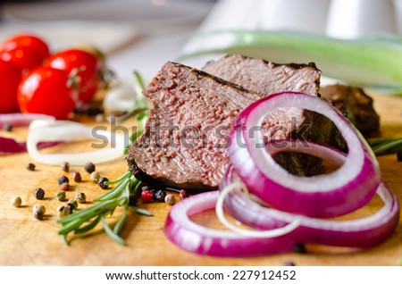 Sliced portion of rare roast beef with red onion rings seasoned with peppercorns and fresh rosemary - stock photo