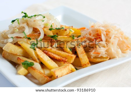 Sliced ??potatoes with onions and sauerkraut on a white square plate
