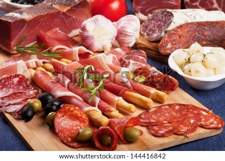 Sliced prosciutto di Parma on wooden board with olives and rosemary - stock photo