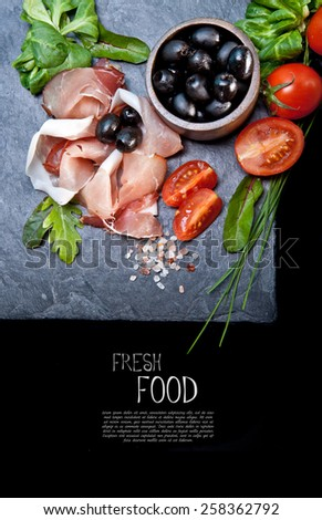 Sliced prosciutto with salad and olive - stock photo